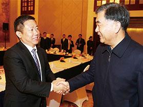 十九届中共中央政治局常委汪洋与周海江握手合影